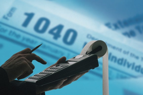 An accountant using a calculator with form 1040 in the background.
