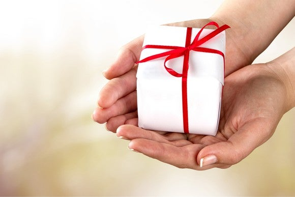 A person with cupped hands holding a wrapped present.