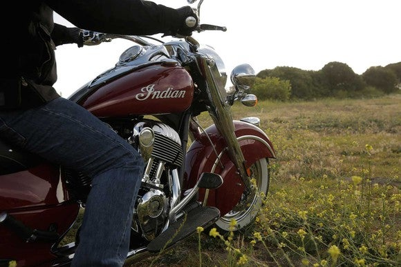 A man sitting on a Polaris Indian motorcycle that's on a field