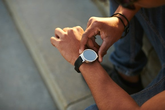 A person presses a button on a smartwatch on his left wrist.