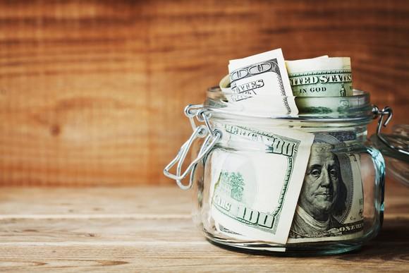A jar of $100 bills sitting on a wood table.