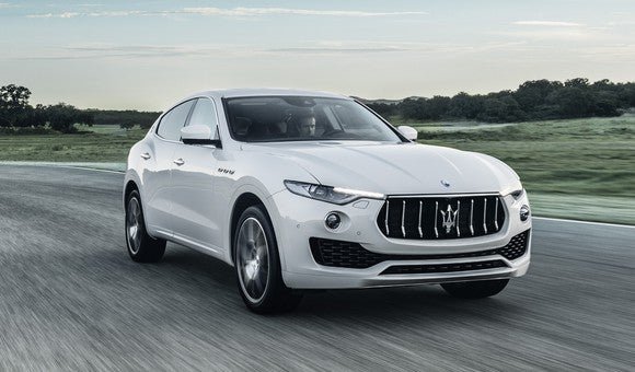 A white Maserati Levante, a midsize luxury SUV, on a country road.