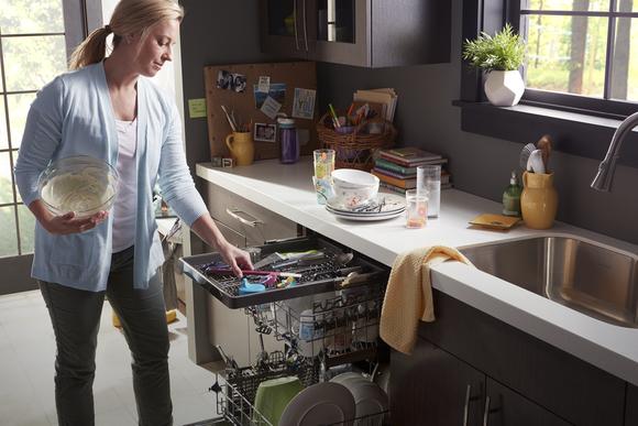 Woman using Whirlpool undercounter dishwasher