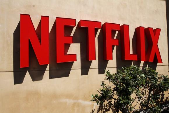 Red Netflix logo on a stucco wall outside the company's headquarters.