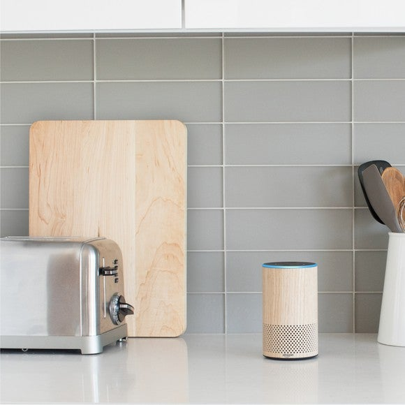 An wooden-looking Amazon Echo on a kitchen counter with toaster, cutting board and mixing spoons.