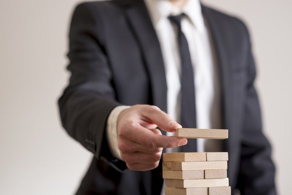 A man in a business suit building a tower of wooden blocks