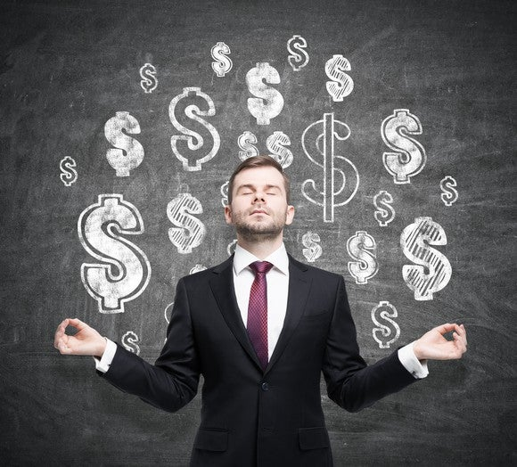 Man meditating in front of dollar signs