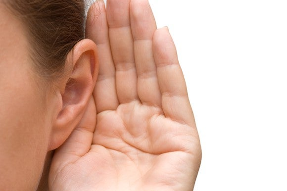 Closeup of a person's hand cupped over their ear