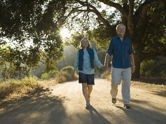 A senior couple holding hands and walking down a dirt road