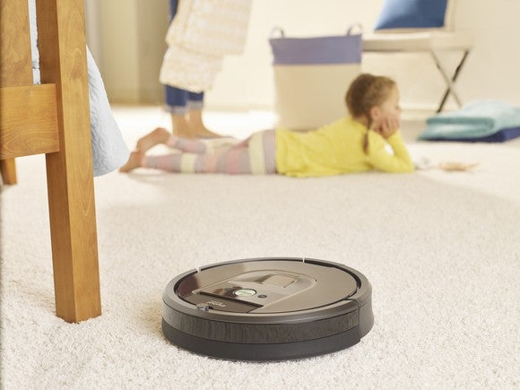 iRobot Roomba 980 cleaning carpet on a carpet next to a wooden chair, with a young girl in the background.