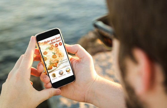 Man ordering pizza on his mobile phone