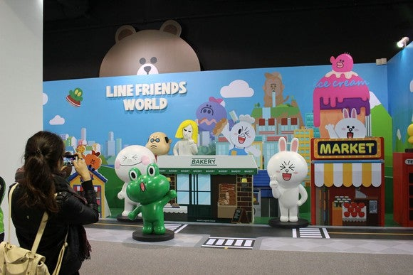 A tourist at the LINE theme park in Taiwan takes a picture of brightly colored cartoon characters.