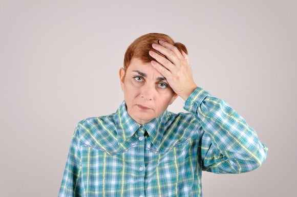 Woman holding her head, looking sheepish