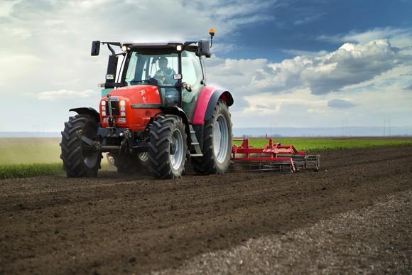 A man drives a tractor through a field.