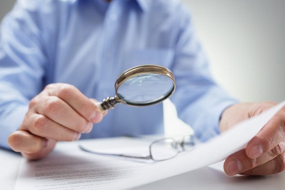 A businessman holds a magnifying glass to a document.