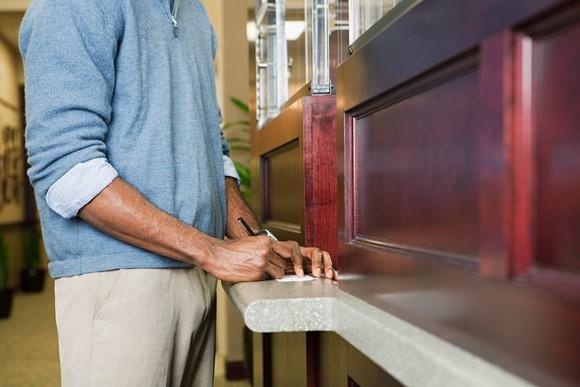 A man at a bank writing a check.