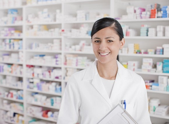 Pharmacist in a white lab coat in front of a set of white shelves with pharmaceuticals on them.