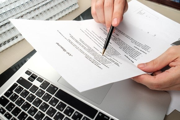 Hand with pen editing a printed resume on top of a laptop.