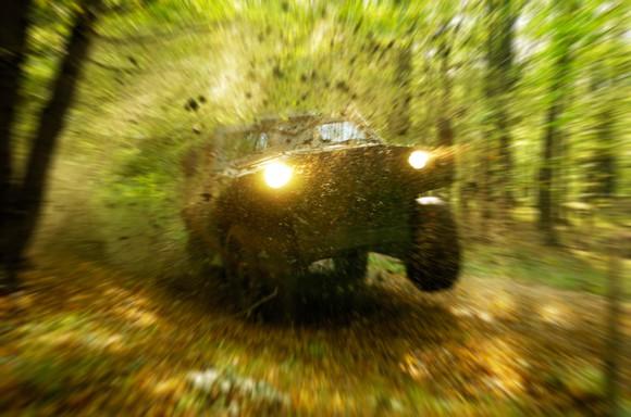 Military all-terrain vehicle speeding through the woods splattering earth.