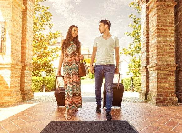 Young couple walking into a hotel with rolling suitcases