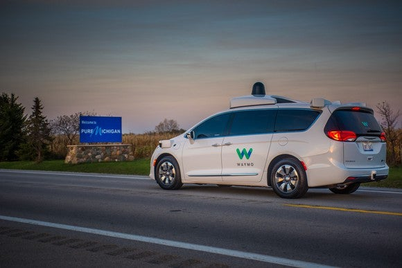 "A white Chrysler minivan with Waymo markings and visible self-driving sensor hardware is shown passing a sign reading ""Welcome to Pure Michigan""."