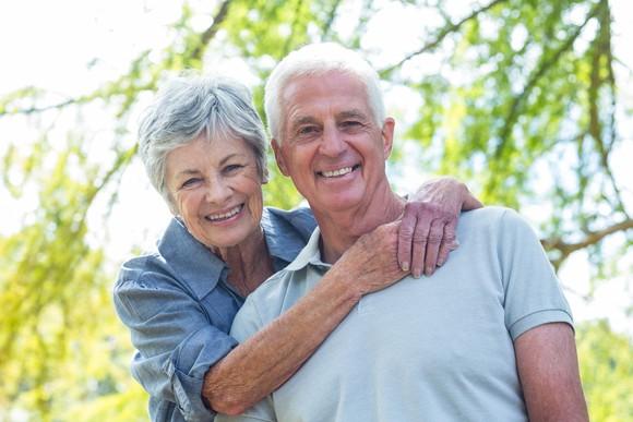Smiling senior woman putting arms around smiling senior man.