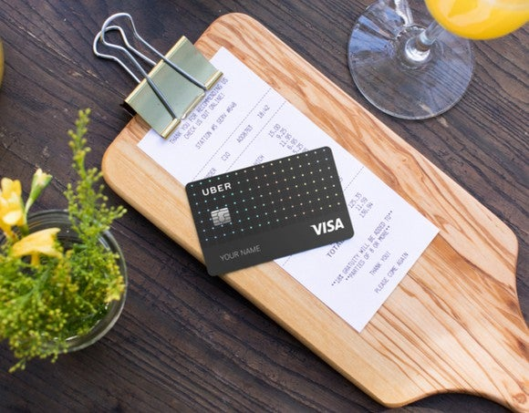 An example Uber Visa Card laying on top of a restaurant check.
