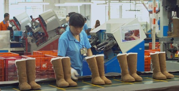 Assembly line with Uggs and a female worker wearing a blue shirt overseeing them.