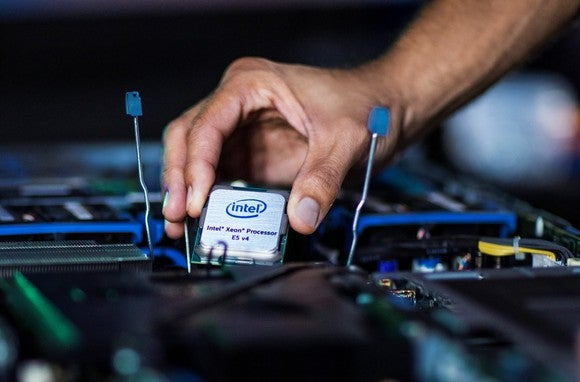 A hand holding an Intel Xeon E5 processor over a motherboard.