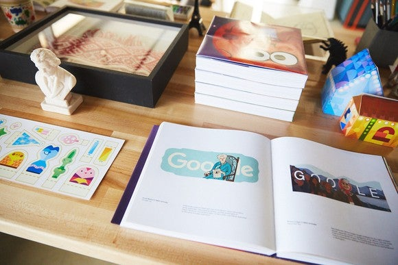 Desk at Google with book open to various Google doodles