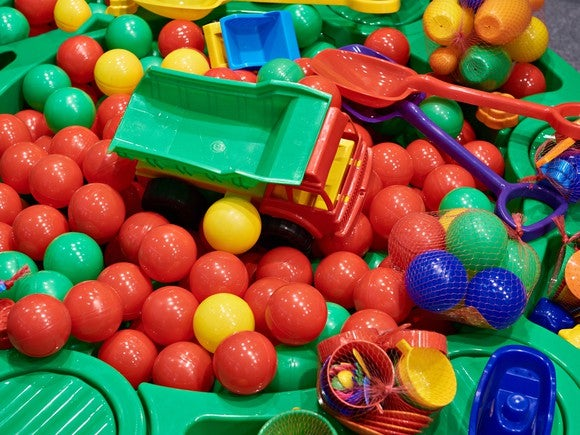 Plastic toy truck, plastic shovels, and other assorted toys in a ball pit.