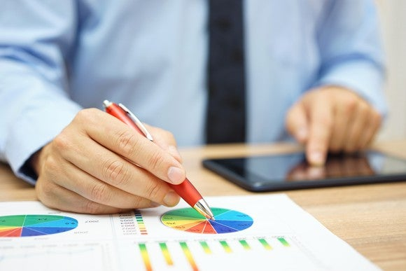A man standing at a desk touches a tablet with one hand and points a pen to a pie chart with the other.
