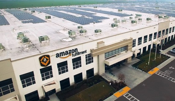 An Amazon fulfillment center, showing off a large roof decked out with hundreds of solar panels.