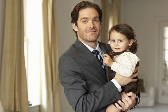 Professionally dressed man holding baby girl