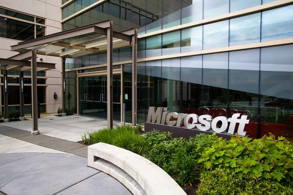 Outside of front entrance of office building with Microsoft sign in a flowerbed.