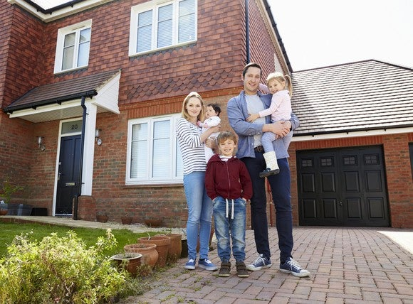 Young family standing in front of their house