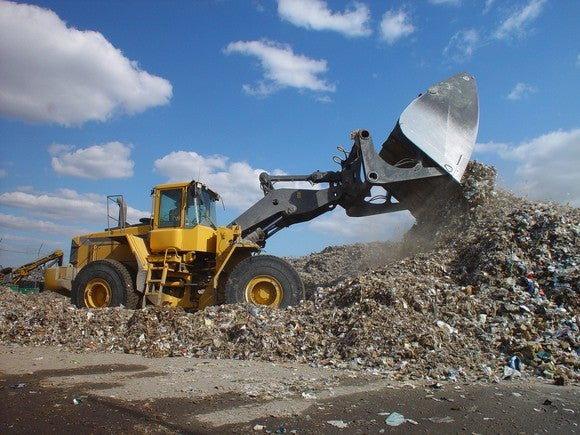 Backhoe loader moving waste in a dump.