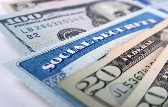 A Social Security card wedged in between a fanned pile of cash bills.