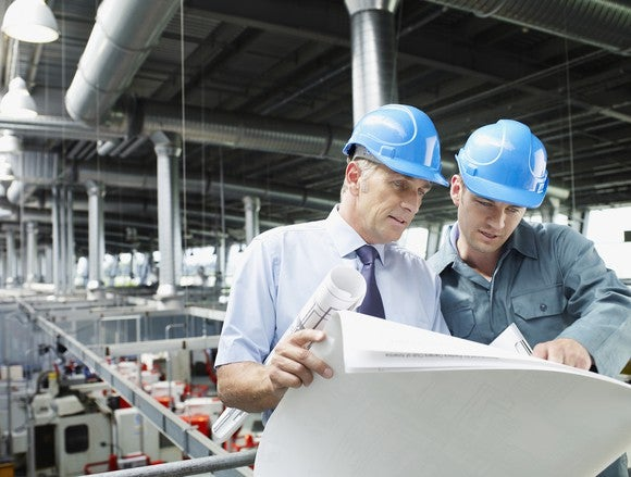 Two men in blue hard hats review documents on a factory floor
