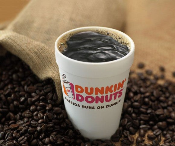 A cup of Dunkin' Donuts coffee sits in coffee beans.