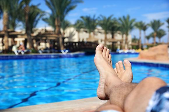 Man's feet next to a sparkling pool