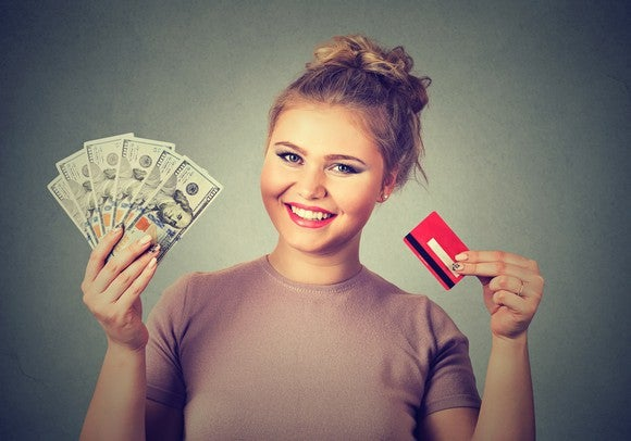 smiling young woman holding credit card in one hand and hundred dollar bills fanned out in the other