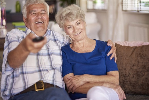 Senior male with TV remove laughing and putting his arm around a senior woman