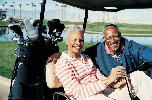 senior man and woman sitting in golf cart smiling