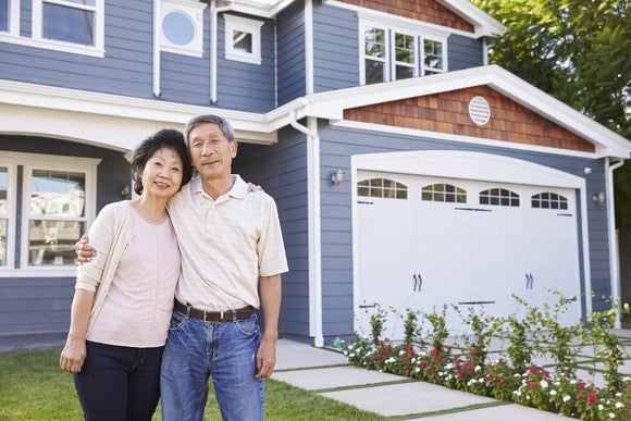 Senior man and woman standing in front of house with arms around each other