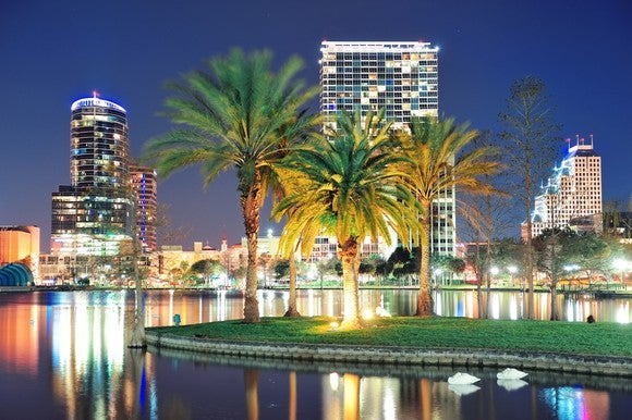 skyline of downtown Orlando at night with palm trees in background
