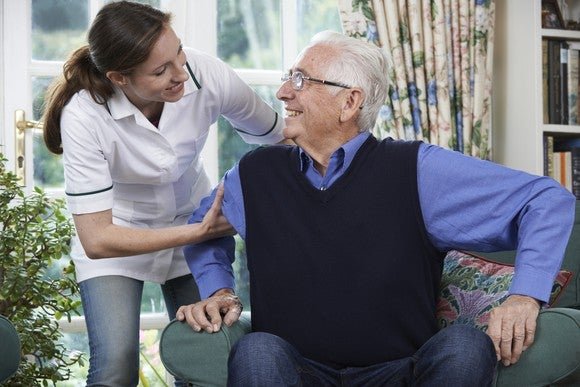 Woman helping senior male get out of a chair