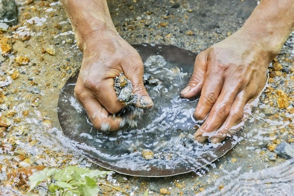 Closeup on two hands panning for gold in a rocky riverbed.
