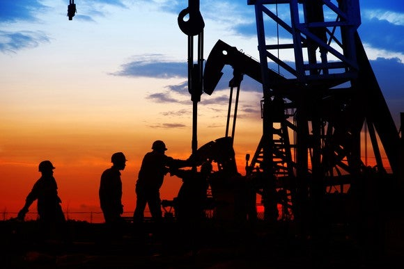 Men in hard hats near a gas rig in silhouette against a sky at sunset.