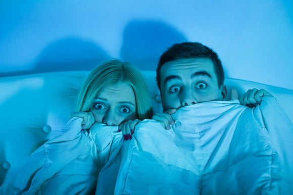 A couple huddles together in bed with scared expressions and covers partly pulled over their faces.